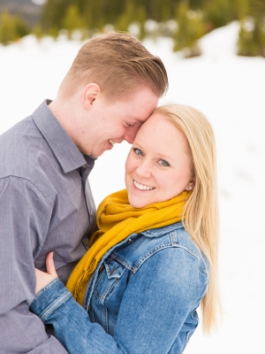 Snowy Bozeman Engagement Session - Couple embracing in mounds of snow