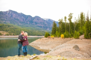 Bozeman Engagement Session in Hyalite Canyon - Couple holding eachother close in front of mountain range