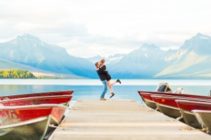 Glacier National Park Engagement Session - Couple kissing on Lake McDonald dock with red boats