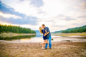 Bozeman Engagement Session in Hyalite Canyon - Couple dipping in front of lake and sky