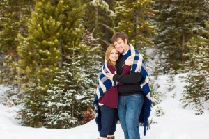 Bozeman Engagement Session - Couple wrapped in blanket on cold winter day in Hyalite Canyon