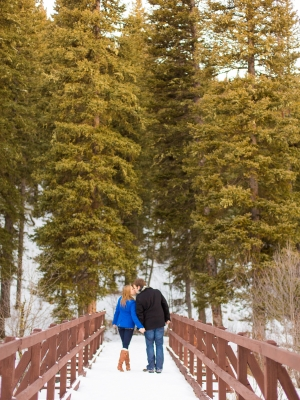Bozeman Winter Engagement Session - Couple walking across Langhor Campground Bridge with tall pines