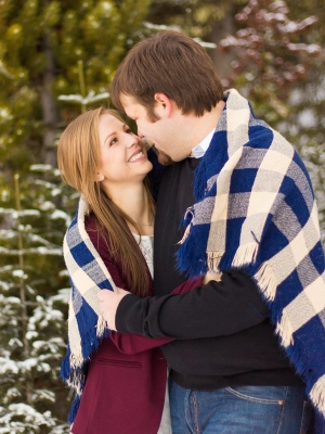 Bozeman Winter Engagement Session - Couple wrapped up in blanket sitting in snow