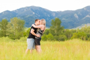 Bridger Mountains Engagement Session - Couple kissing in tall grass in front of Bozeman mountains