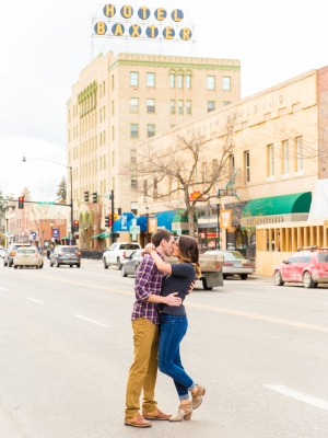 Bozeman Engagement Session in Downtown - Couple kissing in front of Baxter hotel sign on Main Street