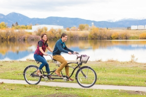 Bozeman Engagement Session at Bozeman Beach - Couple riding bike in front of pond