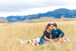 Bozeman Engagement Session in front of Bridger Mountain Range - couple sitting in tall grass