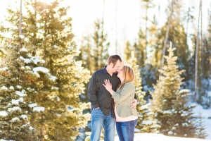 Bozeman Winter Engagement Session - Couple holding each other in front of frigid pine trees