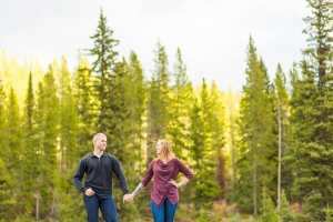 Bozeman Engagement Session - Couple standing posed in front of tall pine trees