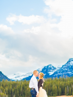 Bozeman Engagement Session - Couple kissing in front of wide range of mountains in Hyalite