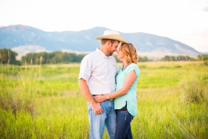 Bozeman Bridger Mountains Engagement Session - Couple standing in front of mountains with cowboy hat