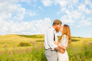 Havre Engagement Session - Sunrise soaked couple kissing in front of green hills