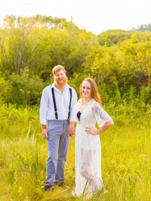 Havre Engagement Session - Sunrise soaked couple standing posed in front of rolling green hills